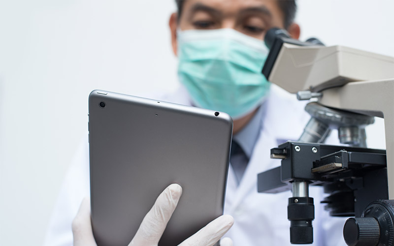 Researcher using a tablet and microscope